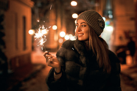 Beautiful young woman in fur coat holding a sparkler enjoys winter Christmas mood in old snowy European city on dark background Stock Photo