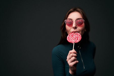 Portrait of a young beautiful stylish girl wearing red drop shaped sunglasses holding a red lollipop and biting it in a seductive sexy way isolated on dark grey background Stok Fotoğraf - 121638486