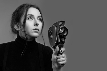 Closeup portrait of a stylish young girl holding an old vintage film novie camera in black and white