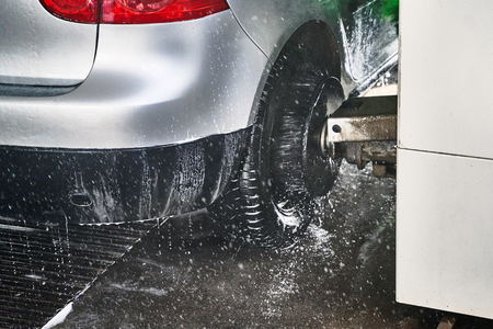 Wheel scrub brush in action at automatic car wash service