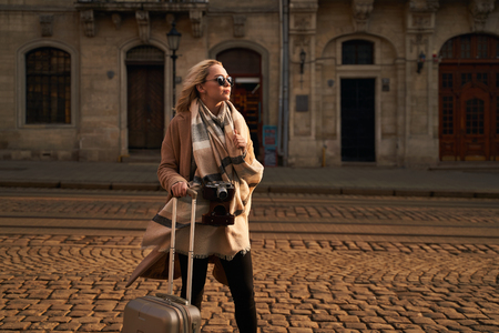 Young beautiful blond woman tourist with a wheeled travel bag and vintage film camera standing on Rynok square in Lviv, Ukraine in the morning