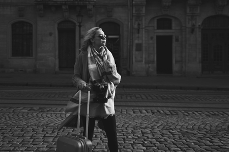 Young beautiful blond woman tourist with a wheeled travel bag and vintage film camera standing on Rynok square in Lviv, Ukraine