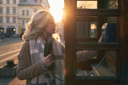 Young beautiful blond woman ready to make an important call in a vintage public phone booth on a sunny evening Stok Fotoğraf