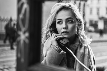 Young beautiful blond woman making an important call in a vintage public phone booth on a sunny evening Stok Fotoğraf - 121638541