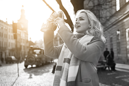 Young beautiful cheerful blond woman taking photos with her vintage film camera on a sunny day at Rynok square in Lviv, Ukraine