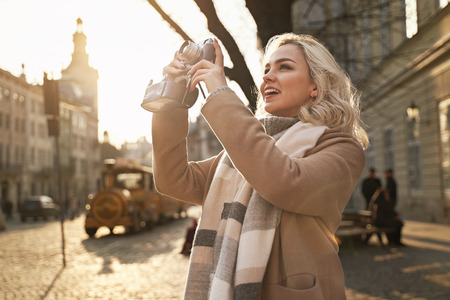 Young beautiful cheerful blond woman taking photos with her vintage film camera on a sunny day at Rynok square in Lviv, Ukraine Stok Fotoğraf - 121638575