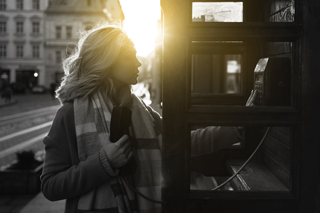Young beautiful blond woman ready to make an important call in a vintage public phone booth on a sunny evening Stok Fotoğraf - 121638579