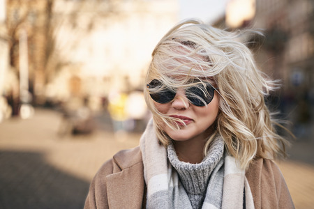 Wind blows ladys blonde hair and covers her face and sunglasses Stok Fotoğraf