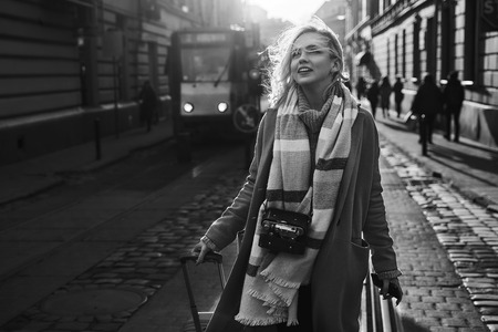 Young beautiful blond woman tourist with a wheeled travel bag and vintage film camera arrives to new city to explore it in black and white