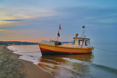 Picturesque landscape of a sunset with a fishing boat on beach in Sopot, Poland. Stok Fotoğraf - 121639625