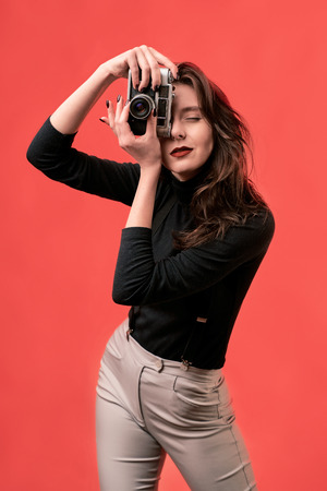 Portrait of a stylish young brunette girl taking a photograph shot with a vintage film photo camera on coral red background Stok Fotoğraf