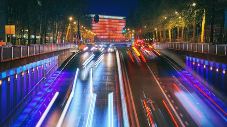 Lange belichtingsopname van een straat in het centrum bij zonsondergang. Wolkenkrabbers op achtergrond met verkeerslichten. Brussel, België. Stockfoto