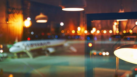 Blurred or defocused beautiful airport terminal early morning or night background with airplane, bokeh lights and glass reflections