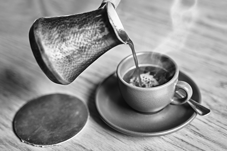 Hot coffee with steam in oriental Turkish style served in cezve, a small long-handled pot with a pouring lip and cup on a wooden table in black and white