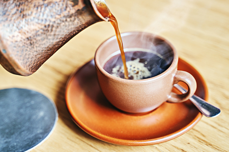Hot coffee with steam in oriental Turkish style served in cezve, a small long-handled pot with a pouring lip and cup on a wooden table