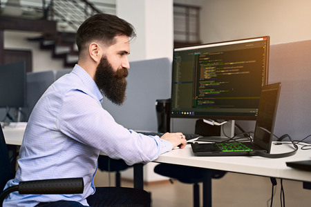 Software programming. Bearded man working on computer in IT office, sitting at desk writing code, working on a project in software development company or startup. High quality image.