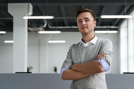 Portrait of a handsome young man professional with arms crossed looking at camera in the IT company office Stok Fotoğraf