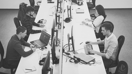 Young professionals working in modern office. Group of developers or programmers sitting at desks focused on computers in IT company open space. Team at work. High quality image.