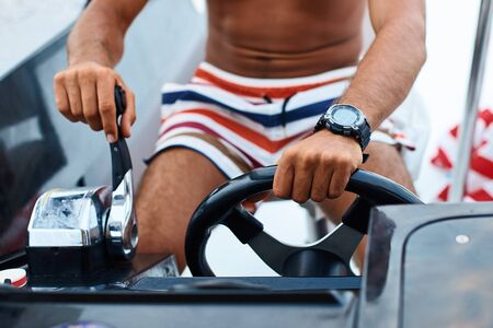 Tanned young handsome captain or skipper steering at the helm and control panel of a yacht with his hands Stok Fotoğraf - 127872309
