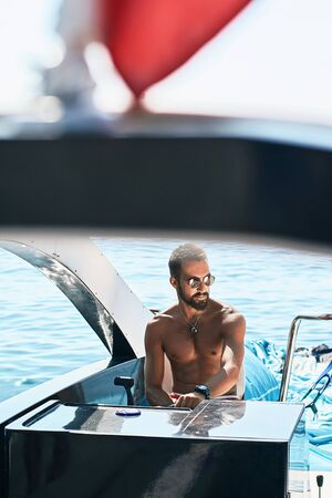 Tanned young handsome bearded muslim captain or skipper steering at the helm and control panel of a yacht under the red flag Stok Fotoğraf