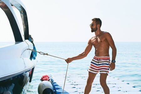 Young handsome muslim captain wearing shorts pulling a rope of a yacht or boat in order to control it standing on berth made of plastic pontoons Stok Fotoğraf - 127872303