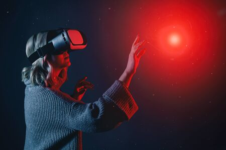 Beautiful young blonde woman wearing a VR glasses touching imaginary object in air during the virtual reality experience Stok Fotoğraf
