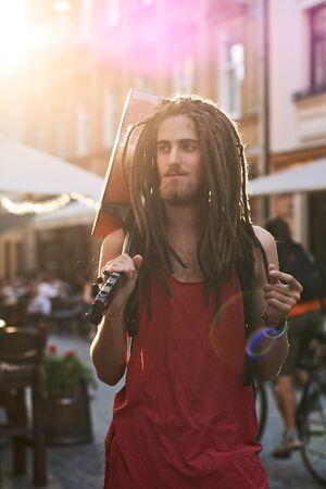 Giovane bell'uomo barbuto hippie con i dreadlocks che schioccano le dita su una vecchia strada della città piena di luce solare con una chitarra Archivio Fotografico