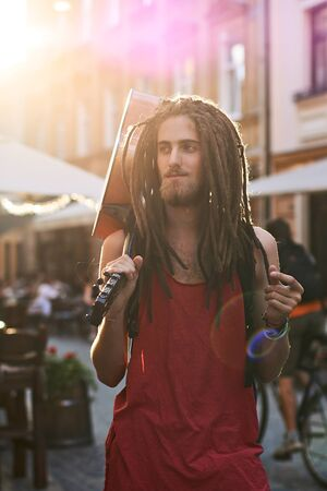 Young handsome bearded man hippie with dreadlocks snapping fingers on an old city street full of sunlight with a guitar Stok Fotoğraf