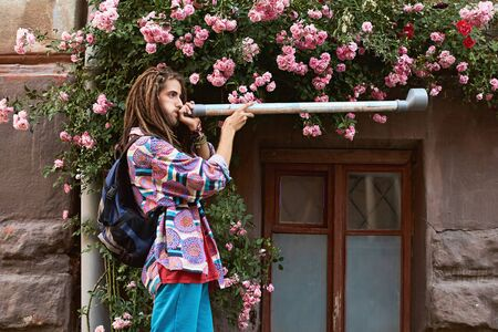 Young handsome bearded man hippie with dreadlocks playing pipe of the pink roses background Stok Fotoğraf - 127872342