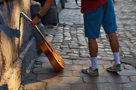 Young hippie musician reaches for his acoustic guitar on the old town street with cobblestones