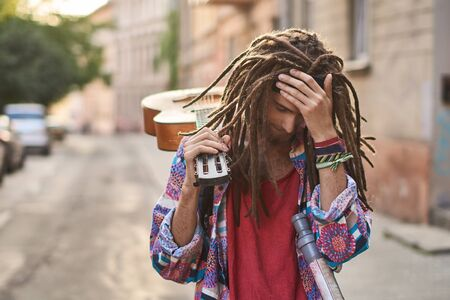 Young handsome bearded man hippie with dreadlocks looks depressed or dramatic