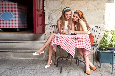 Young beautiful girls dressed in retro vintage style enjoying the old european city lifestyle reading a magazine in street cafe