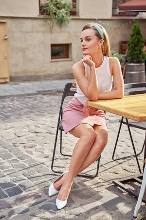 Young beautiful girl dressed in retro vintage style in the old european city sitting on the street cafe wooden table