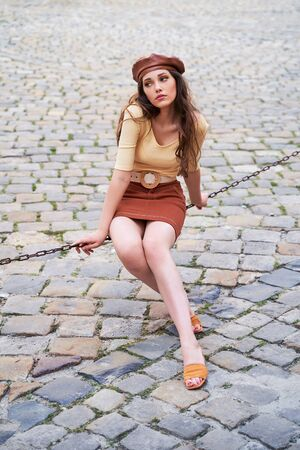 Young beautiful brunette emotional girl dressed in retro vintage style in the old european city sits of a chain waiting for love