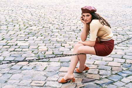 Young beautiful brunette emotional girl dressed in retro vintage style in the old european city sits of a chain thinking Stok Fotoğraf