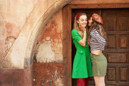 Giovani belle ragazze vestite in stile vintage retrò che si godono lo stile di vita della vecchia città europea e chiacchierano