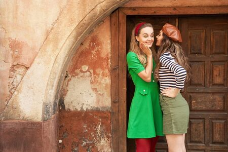 Young beautiful girls dressed in retro vintage style enjoying the old european city lifestyle and chatting