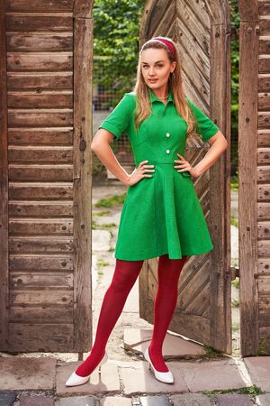 Young beautiful girl dressed in retro vintage style feeling confident standing in the doorway