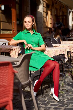 Young beautiful girl dressed in retro vintage style in the old european city sitting in street cafe