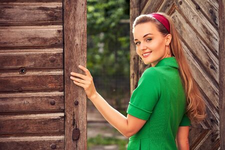 Young beautiful girl dressed in retro vintage style standing by the open wooden door