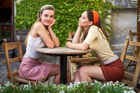 Young beautiful girls dressed in retro vintage style enjoying the old european city lifestyle