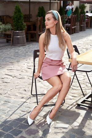 Junges schönes Mädchen im Retro-Vintage-Stil in der alten europäischen Stadt, die auf dem Holztisch des Straßencafés sitzt
