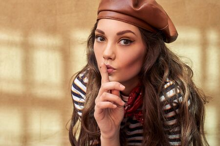 Young beautiful brunette girl dressed in retro vintage style in the old european city makes a hush gesture