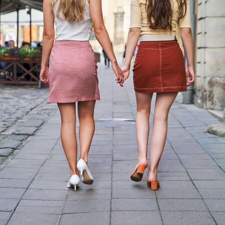 Rear view of two young beautiful girls dressed in retro vintage style enjoying the old european city lifestyle walking the street