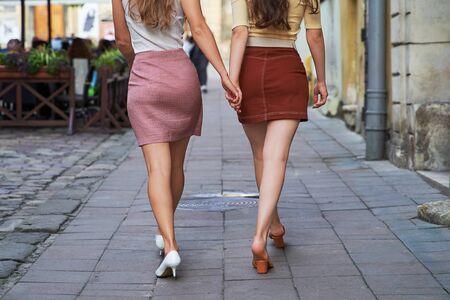 Rückansicht von zwei jungen schönen Mädchen im Retro-Vintage-Stil, die den alten europäischen Stadtlebensstil genießen, der auf der Straße spazieren geht