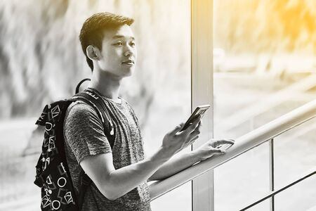 Young asian male student with smartphone in hand wearing a t-shirt and a backpack standing on university stairs and looks optimistic into future in black and white