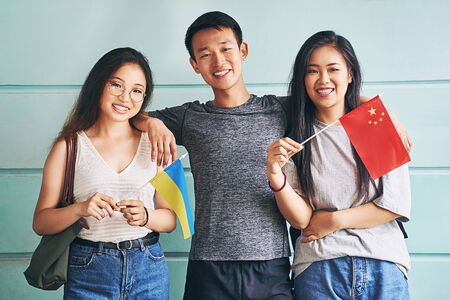 Group of three happy international chinese asian students smiling and holding flags of China and Ukraine in university Stock Photo