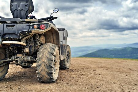 Quadricycle or quad bike on the mountains background on a cloudy day Stok Fotoğraf - 131633860
