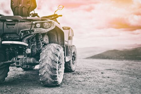 Quadricycle or quad bike on the mountains background on a cloudy day