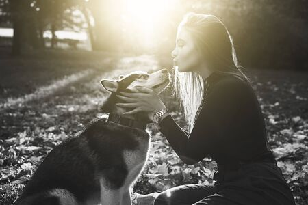 Young beautiful girl playing with her cute husky dog pet in autumn park covered with fallen leaves in black and white